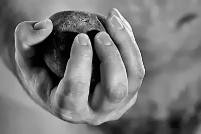 b & w hand holding a stone