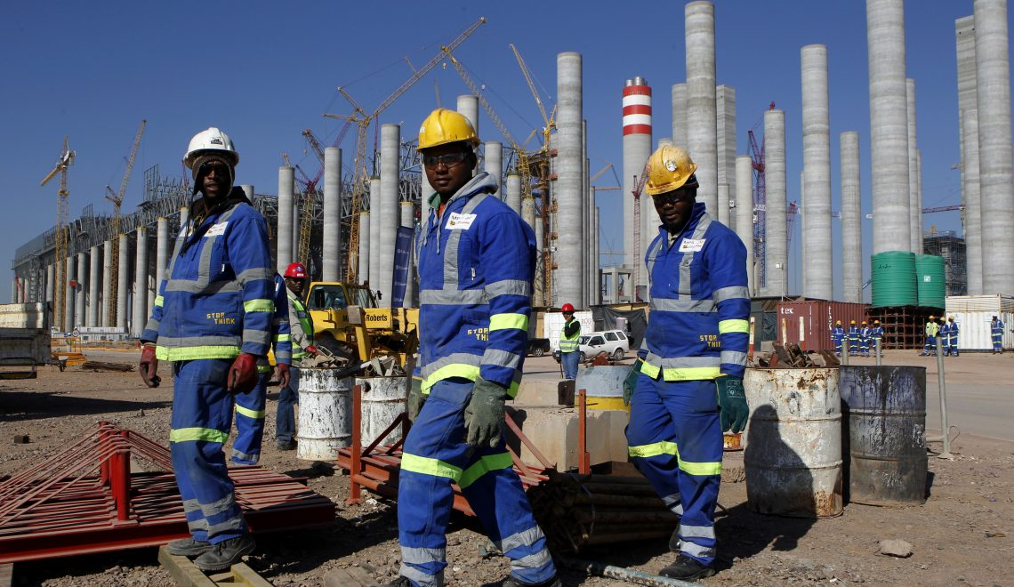 Workers are seen in front the construction site of Eskom's Medupi power station, a new dry-cooled coal fired power station, in Limpopo province, June 8, 2012. South African power utility Eskom reported a nearly 60 percent rise in full-year profit on Thursday owing to higher tariffs and said it would meet power demand during the winter, despite tight supplies. State-owned Eskom, which supplies 95 percent of South Africa's power, said profit in the year to end-March rose to 13.2 billion rand($1.58 billion) from 8.4 billion the previous year. Picture taken June 8, 2012. REUTERS/Siphiwe Sibeko (SOUTH AFRICA - Tags: ENVIRONMENT ENERGY BUSINESS)